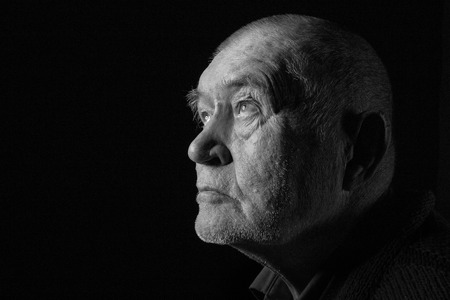 old senior man looking up in dark monochrome image photo