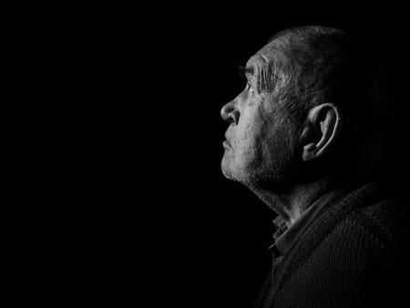 old senior man looking up praying in dark monochrome image photo