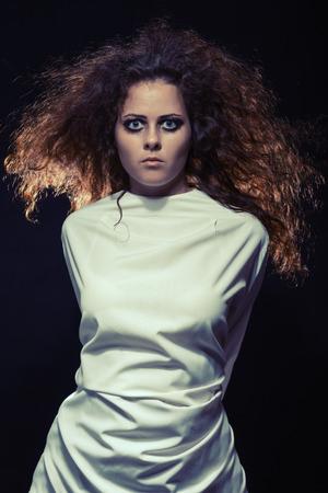 sad crazy woman in straik jacket standing at dark toned image photo