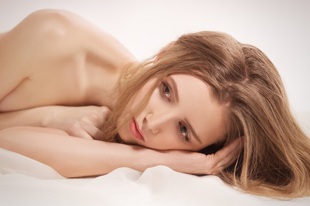sensual young woman lying in bed Stock Photo