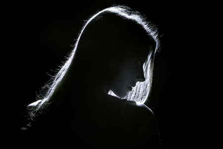 sad woman profile silhouette in dark Standard-Bild