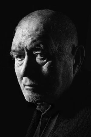 man senior on black background looking at camera, monochrome photo