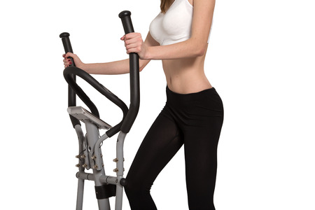 home trainer: slim unrecognizable woman walks on home elliptical trainer isolated