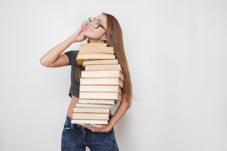 stacked books: happy girl with stacked books in hands on white background Stock Photo