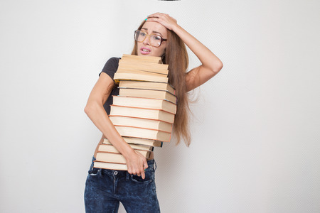 shocked girl with stacked books in hands isolated on white background photo