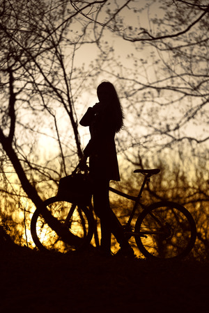 woman with bike silhouette at sunset photo