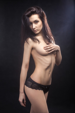 luxury bared woman in panties on black background toned image photo