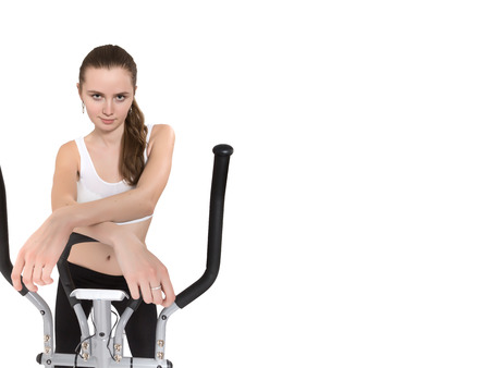 home trainer: slim beautiful woman posing on home elliptical trainer isolated Stock Photo