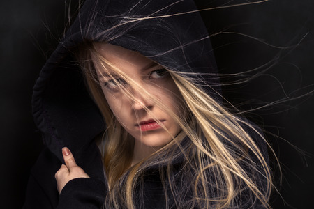 scared girl: scared girl in black hood in dark
