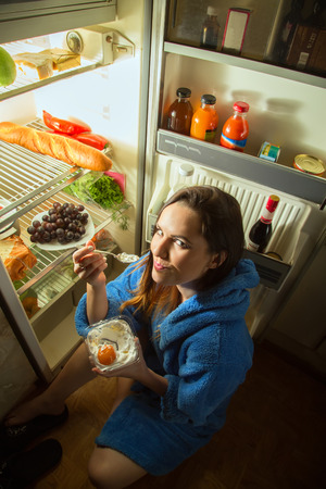 refrigerator: woman eating dessert near refrigerator Stock Photo