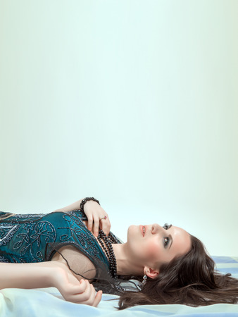one adult only: beautiful woman thinker lying on cyan background with copyspace