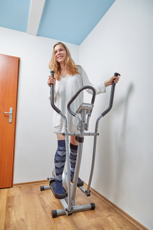 home trainer: pretty woman working on home elliptical trainer