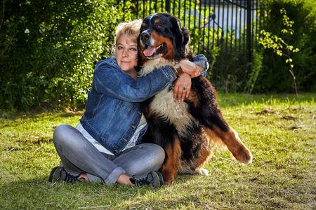 bernese mountain dog: mature woman embracing her bernese mountain dog