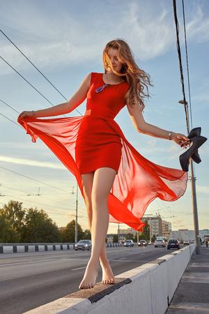 happy woman barefoot walking in city sunset Foto de archivo