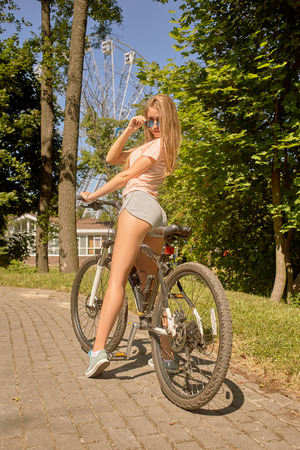 road cycling: pretty woman posing with bike in sunny park Stock Photo