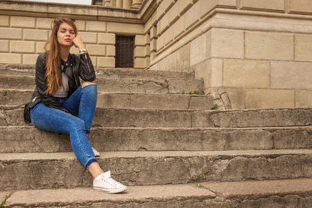 the thinker: Portrait of a serious woman thinker sitting on steps