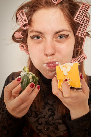 gluttonous: Young hungry gluttonous woman eating pie and cucumber