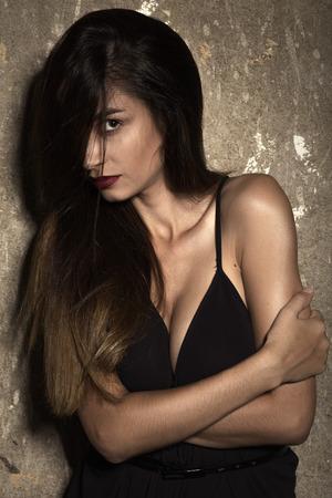 big boobs: sensual woman with big breast near grunge wall Foto de archivo