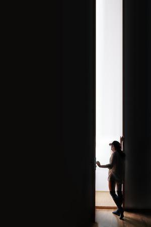 PUERTA: mujer entrar a un espacio en blanco de la oscuridad, la imagen con copyspace Foto de archivo