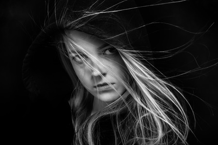 scared girl: scared girl in black hood looking back in dark monochrome Stock Photo