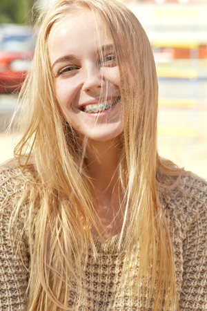 toothy smiles: happy woman with braces and long hair smiling