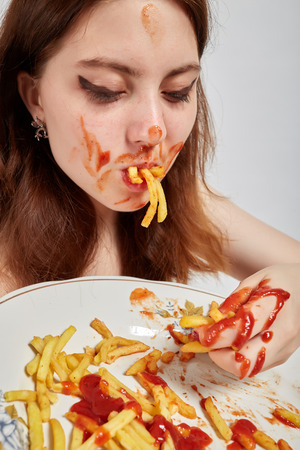 french ethnicity: Fun Woman Eats Fried Potatoes Stock Photo