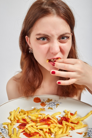 french ethnicity: Fun Woman Eats French Fries Stock Photo