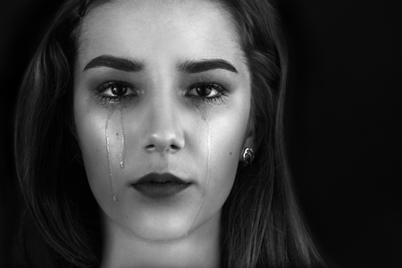crying: beautiful woman crying on black background, monochrome Stock Photo