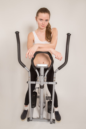 home trainer: slim woman posing near home elliptical trainer Stock Photo
