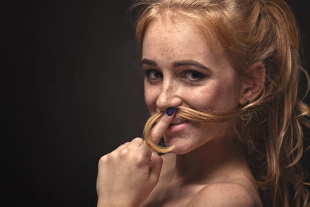 blonds: fun young woman making mustache from her hair Stock Photo