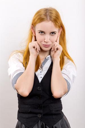 gestos de la cara: diversi�n chica muestran o�dos en el fondo blanco Foto de archivo