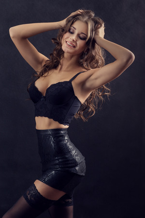 strip tease: luxury attractive happy woman on black background