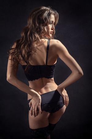 prostituta: mujer bonita en ropa interior y medias muestra sus nalgas en el fondo negro Foto de archivo