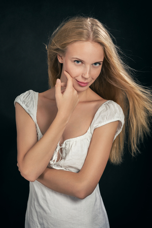 only adult: smiling blond girl in white dress on black background