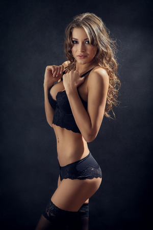 attractive woman in lingerie on black background Stockfoto