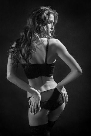 pretty woman in lingerie and stockings shows her buttocks monochrome image