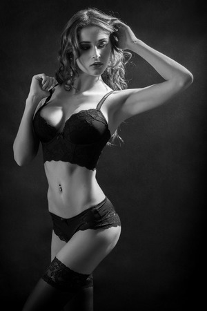fetishes: luxury woman in lingerie on black background looking back, monochrome