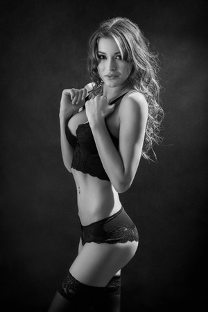 fetishes: attractive woman in lingerie on black background, monochrome Stock Photo