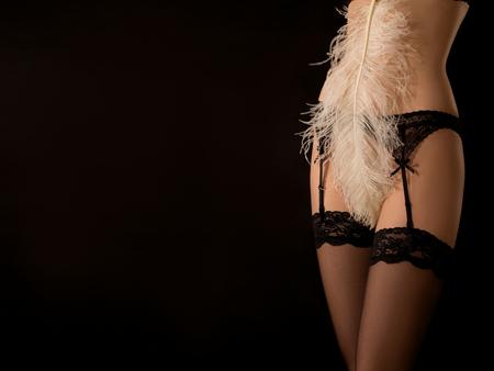 jolie femme dans les bas couvrant son corps nu avec plume blanche sur fond noir avec copyspace Banque d'images