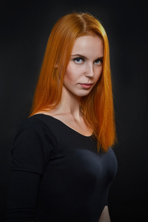 young girl nude: serious woman with red hair on black background