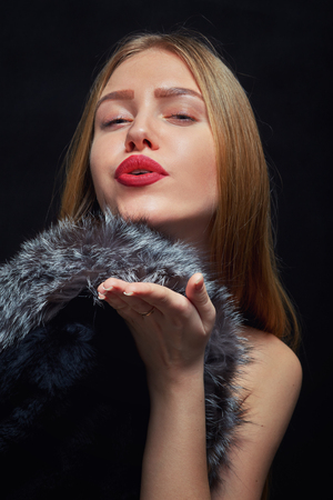 sexy kiss: luxury girl with fur send kiss on black background
