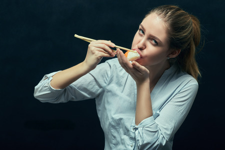 chinese lady: girl eating sushi roll on black background
