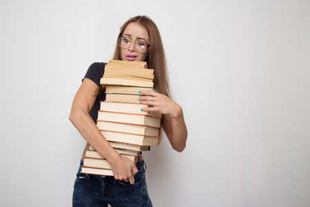 stacked books: shocked girl with stacked books in hands on white background Stock Photo