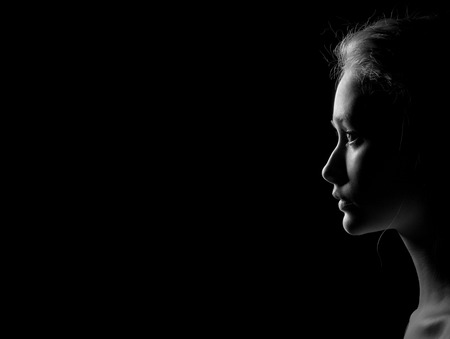 adult nude: profile of young pensive woman with red hairs on black background with copyspace, monochrome