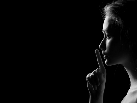adult nude: Young Woman Gesturing For Being Quiet, Shows Silence Sign In Dark Background With Copyspace, monochrome image