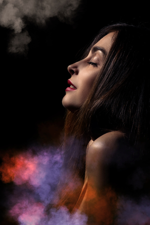 sex activity: sensual aroused woman on black background with smoke