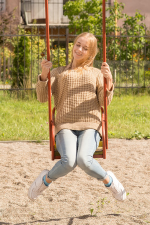 swinging: happy girl with lollipop on playground swinging