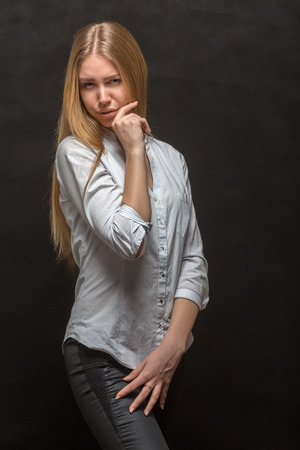 cynical: young woman in skeptical pose on black background