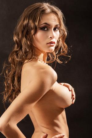 tetas: hermosa chica desnuda muestra su pecho grande sobre fondo negro