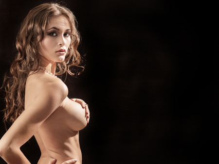 beautiful naked girl show her big breast on black background, image with copyspace